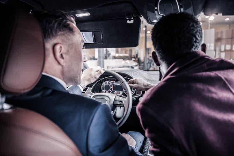 Homem de negócios maduro que senta-se atrás da roda perto de seu consultante do carro foto de stock royalty free