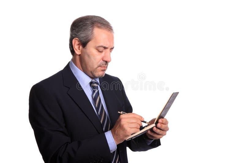 Homem de negócios maduro que toma notas fotografia de stock