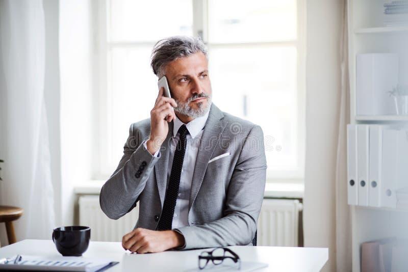 Homem de negócios maduro sério com o smartphone que senta-se na tabela, fazendo um telefonema fotos de stock royalty free
