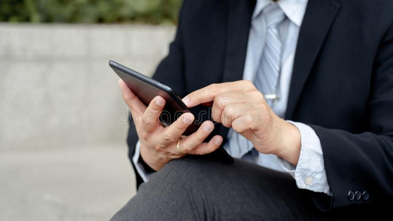 Homem de negócios maduro superior que usa a tabuleta digital em um exterior imagem de stock royalty free