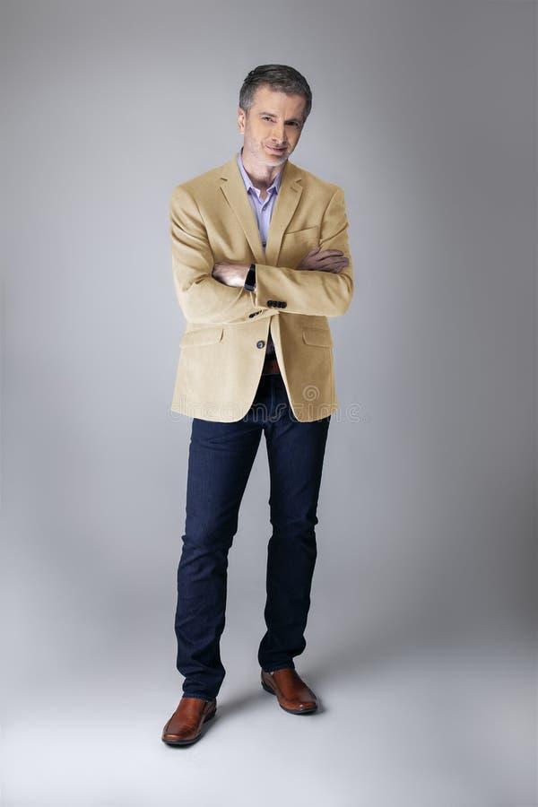 Homem de negócios maduro Wearing um revestimento colorido bege ou de creme imagem de stock