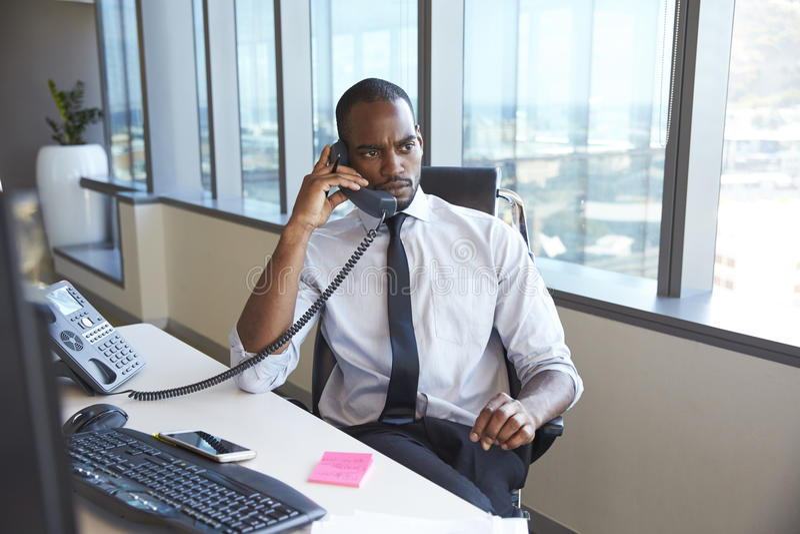Homem de negócios Making Phone Call que senta-se na mesa no escritório imagem de stock