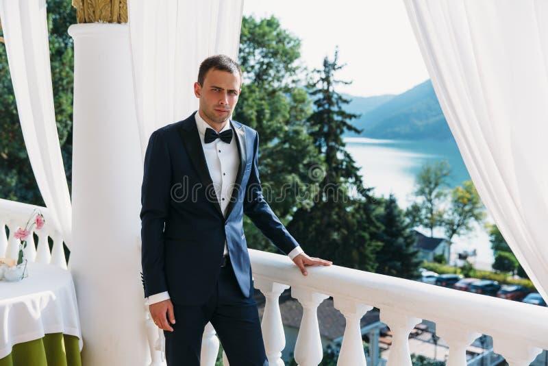 Homem de negócios masculino novo em um terno preto clássico com uma camisa branca e um laço Retrato da espera do noivo foto de stock