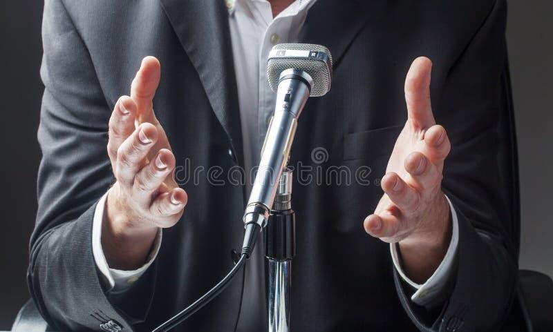 Homem de negócios masculino que fala ao público no micro imagens de stock