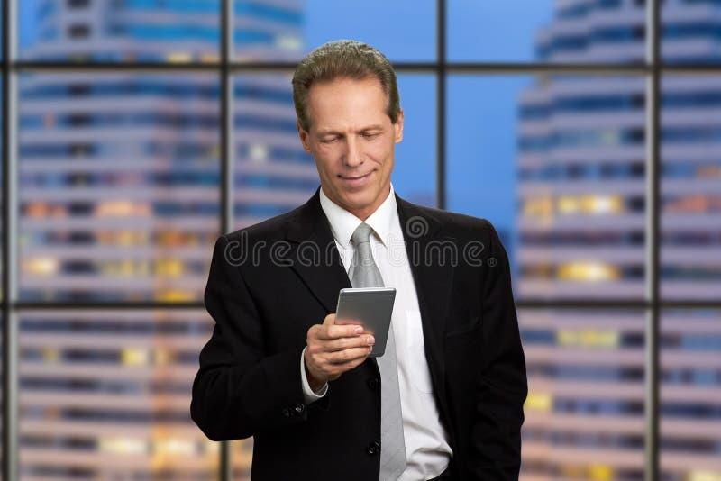 Homem de negócios de meia idade que olha seu smartphone fotografia de stock