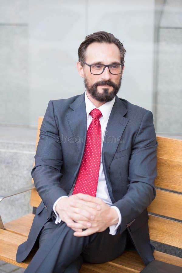 Homem de negócios de meia idade que toma a ruptura de relaxamento no banco Série da vida urbana de pessoas do negócio Retrato do  fotos de stock royalty free
