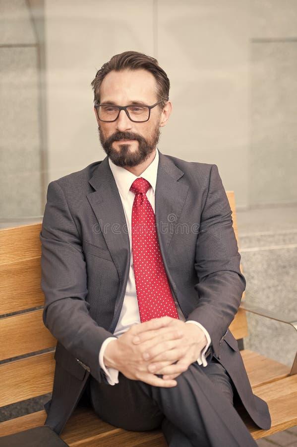 Homem de negócios de meia idade que toma uma ruptura de relaxamento no banco Série da vida urbana de pessoas do negócio Retrato d fotografia de stock