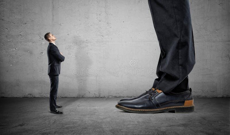 Homem de negócios minúsculo que olha acima nos pés enormes de um outro homem fotos de stock