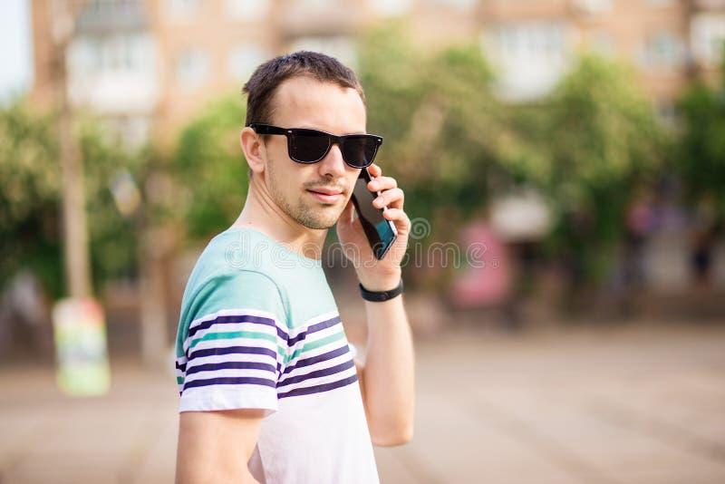 Homem de neg?cios moderno do moderno consider?vel com barba que anda na cidade e que chama o telefone imagem de stock royalty free
