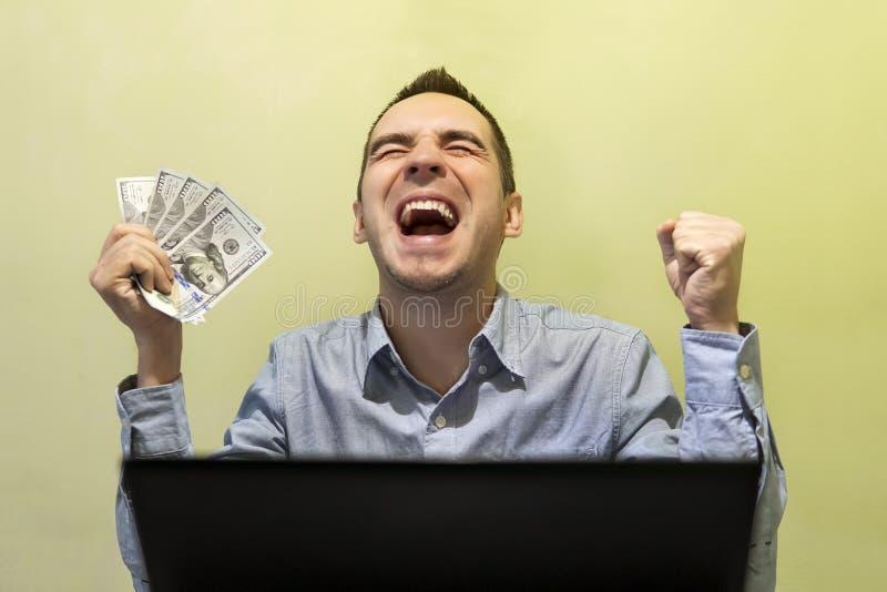 Homem de negócios moderno novo entusiasmado com seu sucesso ao trabalhar imagem de stock
