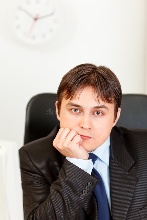 Homem de negócios moderno pensativo que senta-se na mesa de escritório fotos de stock royalty free