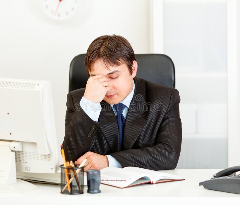 Homem de negócios moderno Tired que senta-se na mesa de escritório fotografia de stock royalty free