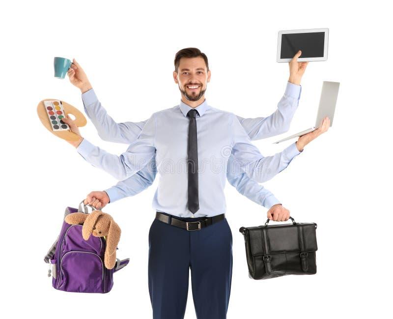 Homem de negócios de Multitask com muitas mãos que guardam o material diferente no fundo branco imagem de stock royalty free