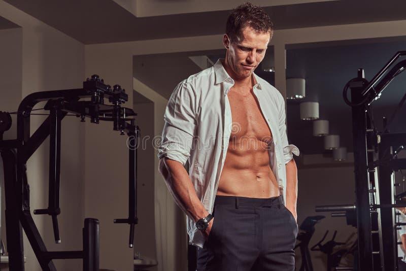 Homem de negócios muscular considerável cansado em uma camisa desabotoada que está no gym foto de stock