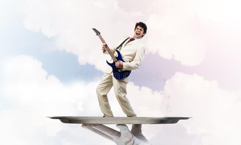 Homem de negócios na bandeja do metal que joga a guitarra elétrica contra o fundo do céu azul imagens de stock