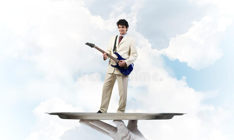 Homem de negócios na bandeja do metal que joga a guitarra elétrica contra o fundo do céu azul fotos de stock royalty free