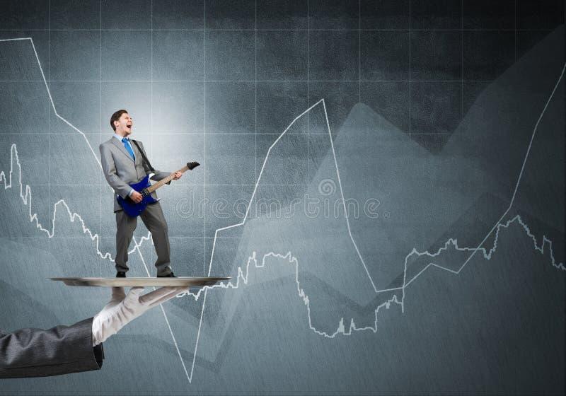 Homem de negócios na bandeja do metal que joga a guitarra elétrica contra a parede com fundo das cartas imagens de stock