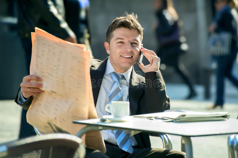 Homem de negócios na barra da rua que tem a notícia do jornal da leitura do café do café da manhã que fala no telefone celular fotos de stock