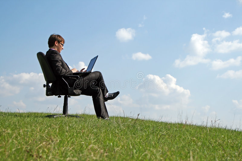 Homem de negócios na cadeira do escritório que trabalha com um portátil fotos de stock royalty free
