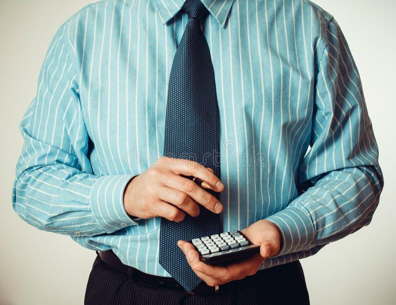Homem de negócios na camisa azul com calculadora imagens de stock