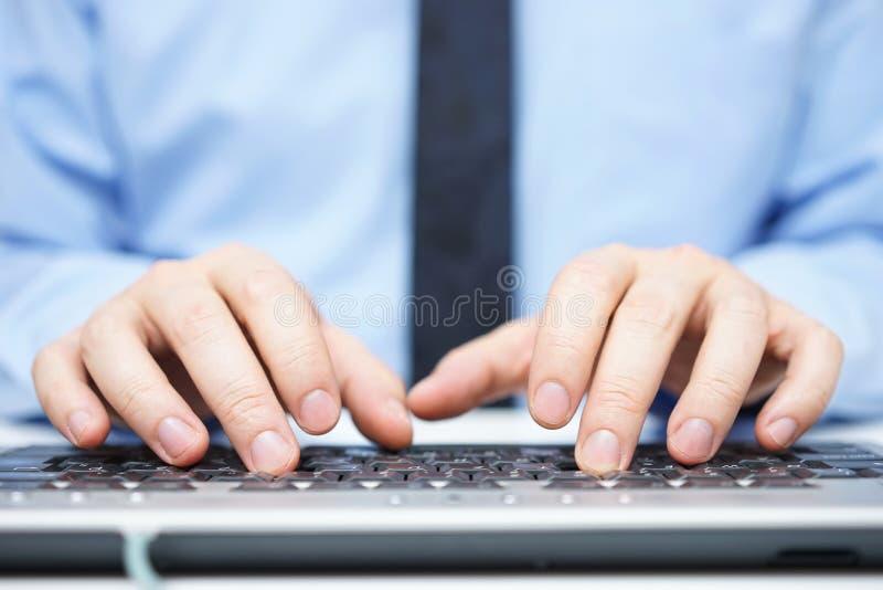 Homem de negócios na camisa azul que datilografa no teclado de computador fotos de stock