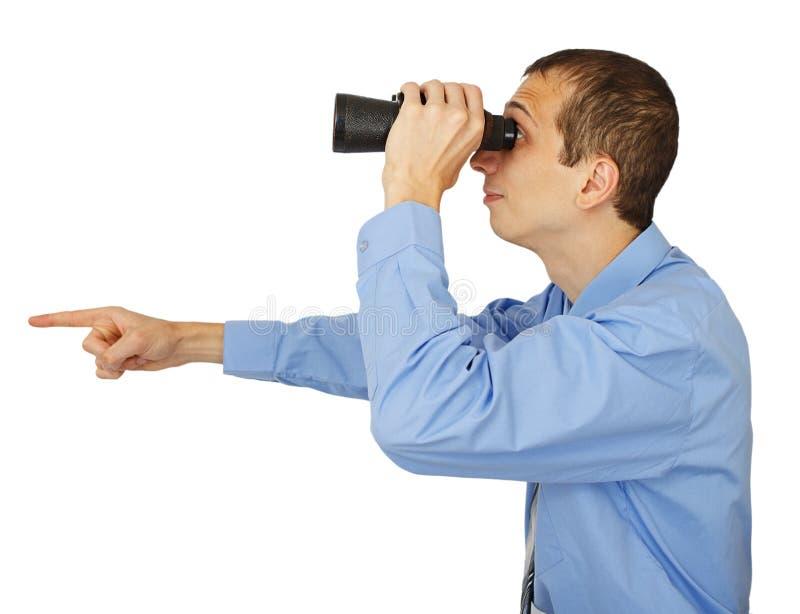 Homem de negócios na camisa azul que olha com seus binocular e pointin fotografia de stock royalty free