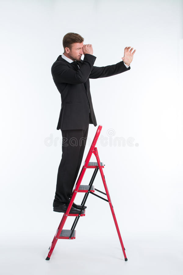 Homem de negócios na escada usando o telescópio imagem de stock