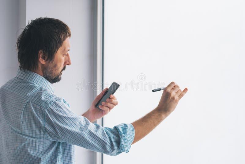 Homem de negócios na escrita do escritório no whiteboard imagens de stock royalty free