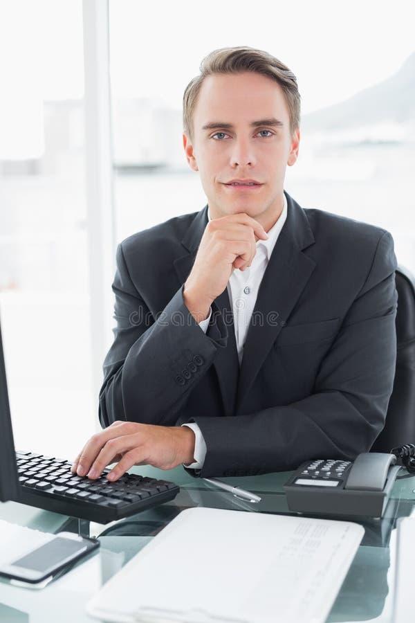 Homem de negócios na frente do computador na mesa de escritório fotos de stock