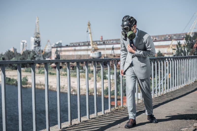 homem de negócios na máscara de gás que anda na ponte, conceito da poluição do ar imagens de stock royalty free