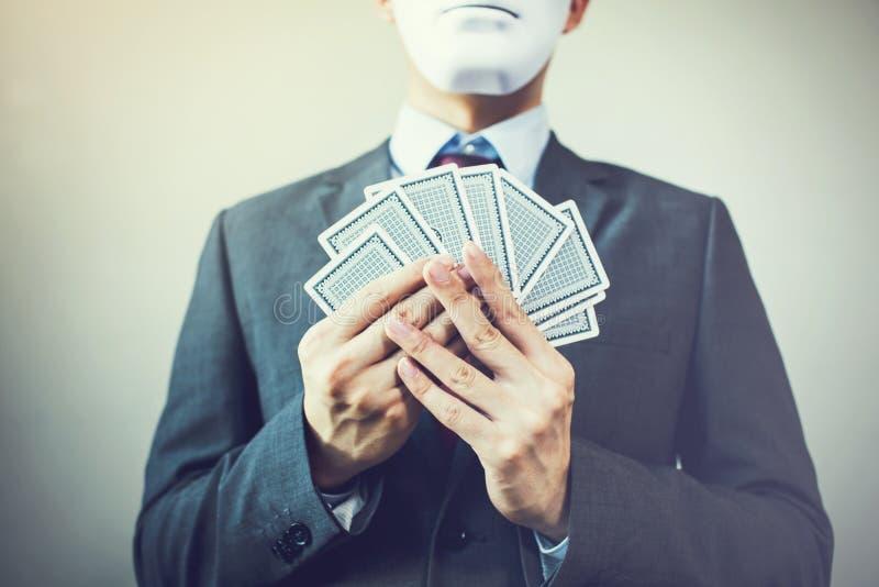 Homem de negócios na máscara que guarda um grupo de cartões de jogo - expressão escondendo no conceito estratégico da competição  fotos de stock