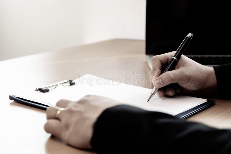 Homem de negócios na mesa de escritório que assina um formulário do contrato no escritório fotos de stock