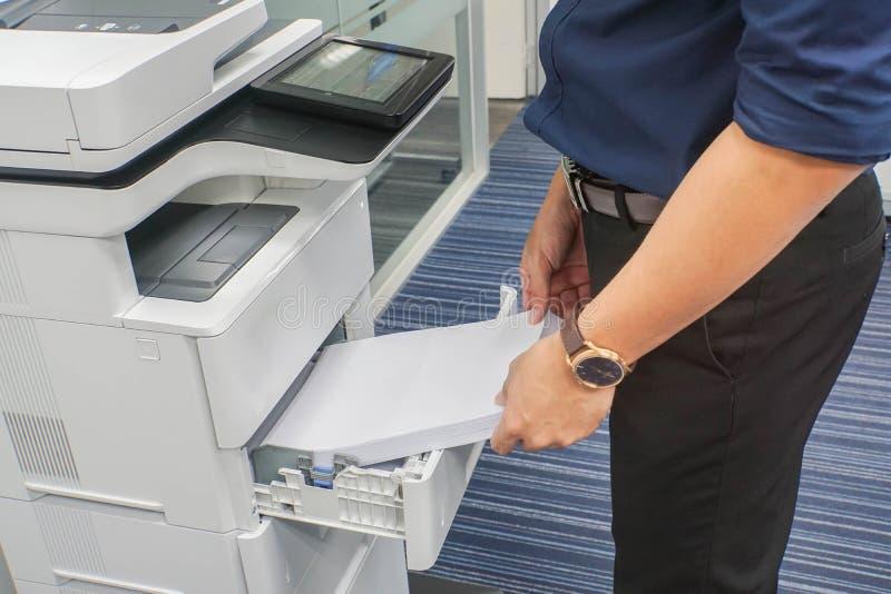 Homem de negócios na obscuridade - folha azul do papel da inserção A4 da camisa na bandeja da impressora de escritório foto de stock