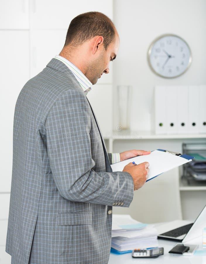 Homem de negócios na roupa do escritório que enche-se acima dos originais fotografia de stock