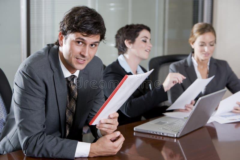 Homem de negócios na sala de reuniões com colegas fêmeas foto de stock