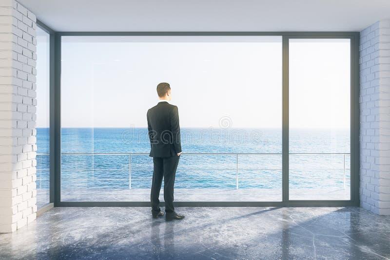 Homem de negócios na sala vazia do sótão com a janela grande no assoalho e no ocea imagens de stock