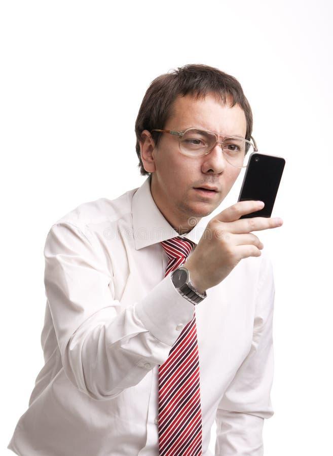 Homem de negócios Nerdy que prende um smartphone foto de stock