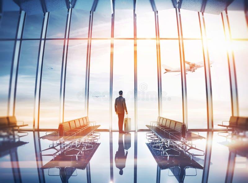 Homem de negócios no aeroporto com mala de viagem fotos de stock royalty free