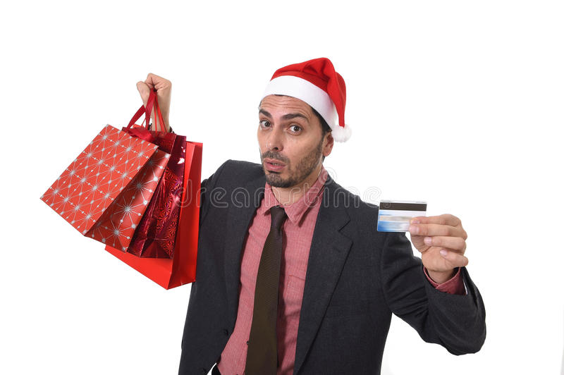 Homem de negócios no chapéu de Santa Claus Christmas que guarda sacos ensopados e cartão de crédito no preocupado e esforço imagens de stock