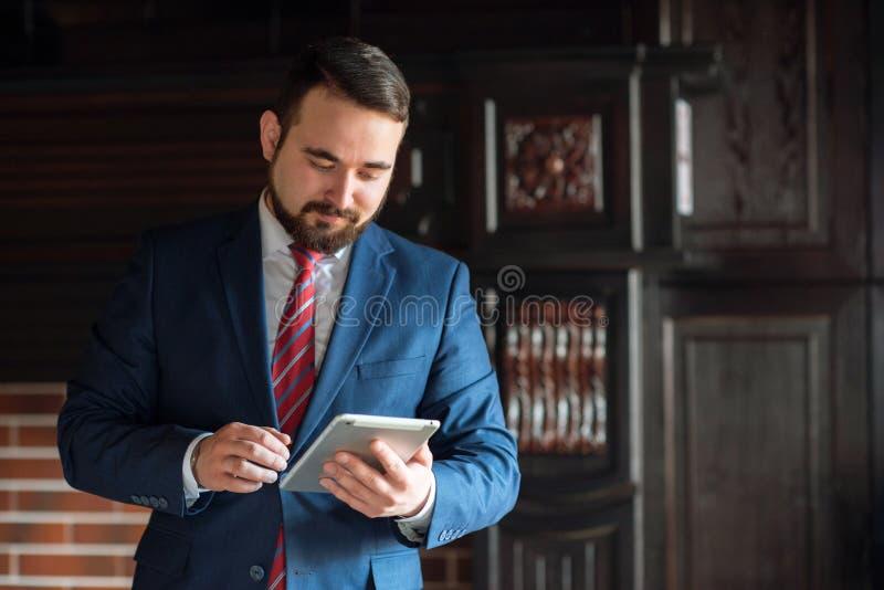 Homem de negócios no escritório que trabalha na tabuleta fotografia de stock royalty free