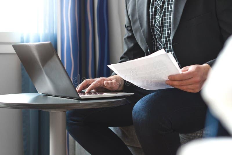 Homem de negócios no papel do relatório comercial da leitura da sala de hotel imagens de stock