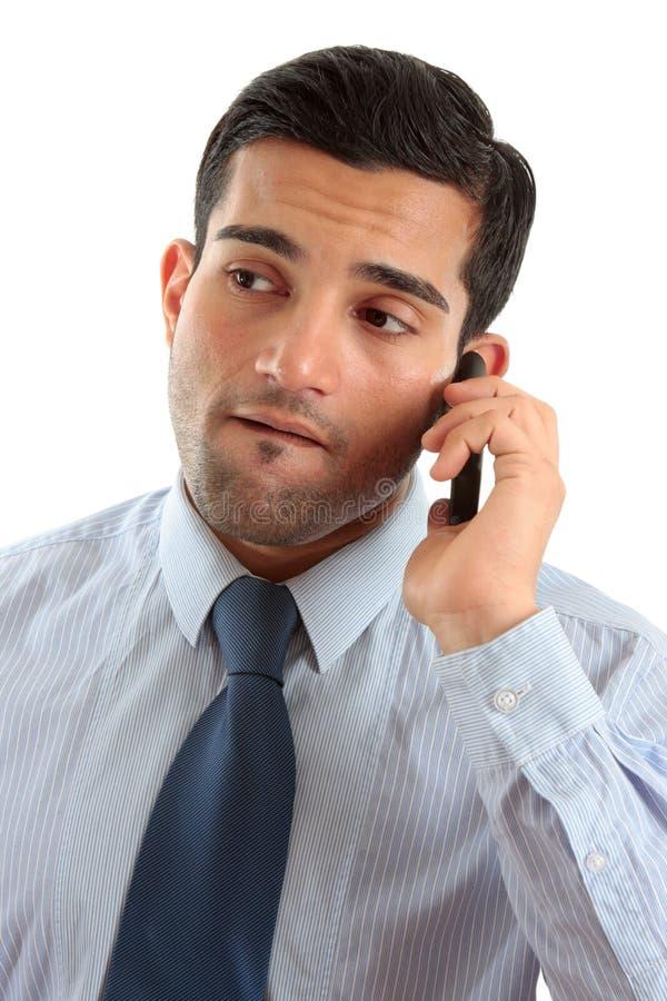 Homem de negócios no pensamento do telefone móvel imagens de stock royalty free
