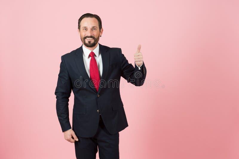 Homem de negócios no polegar escuro do terno acima no fundo pastel cor-de-rosa isolado no estúdio fotos de stock