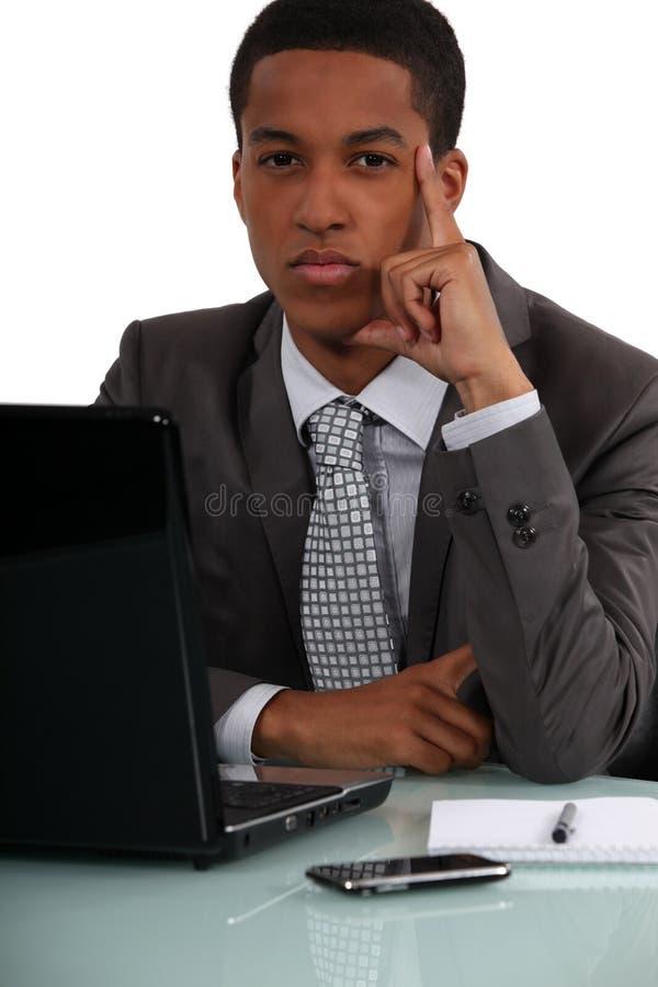 Homem de negócios no seu pensamento da mesa fotografia de stock