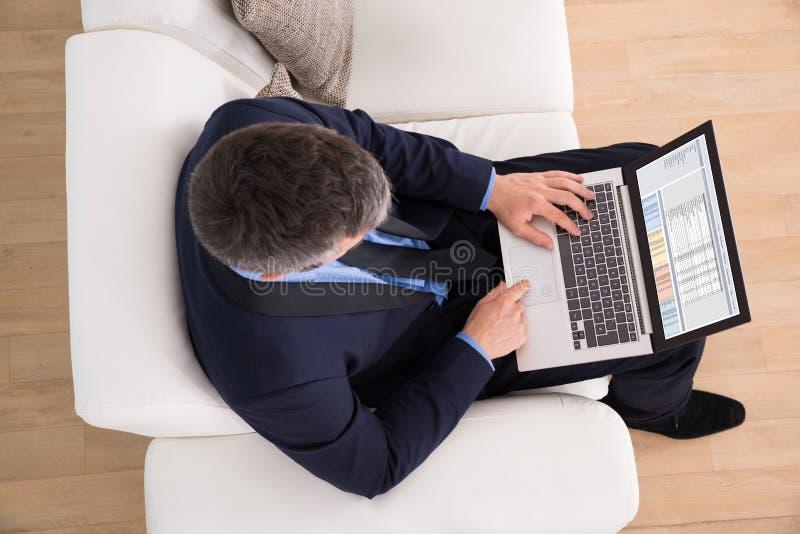 Homem de negócios no sofá usando o portátil imagem de stock royalty free