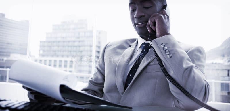 Homem de negócios no telefone ao ler um original fotografia de stock royalty free