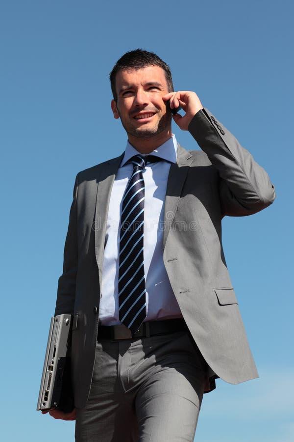 Homem de negócios no telefone no céu azul imagem de stock royalty free