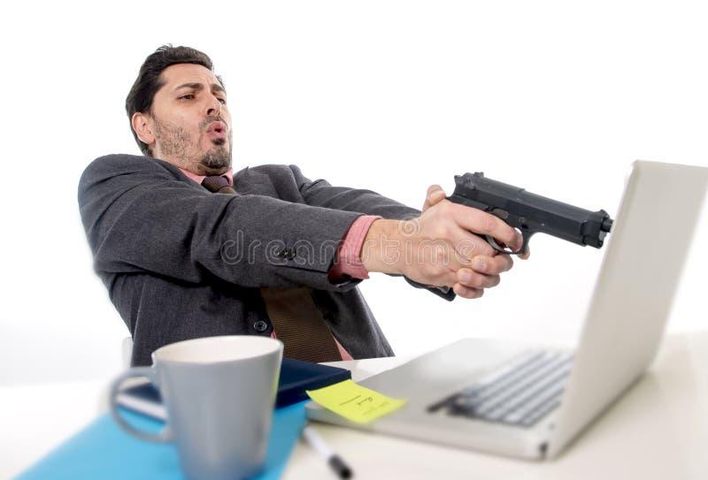 Homem de negócios no terno e laço que senta-se na mesa de escritório que trabalha no computador que apontam a arma ao portátil em fotografia de stock royalty free