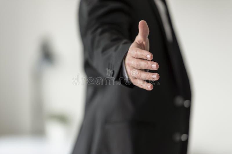 Homem de negócios no terno de negócio preto que oferece lhe um aperto de mão imagens de stock