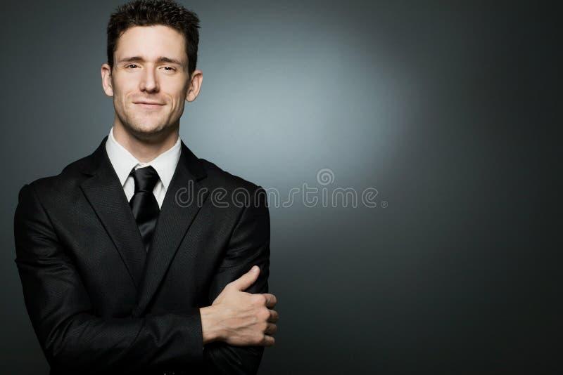 Homem de negócios no terno preto que expressa o positivity. imagem de stock